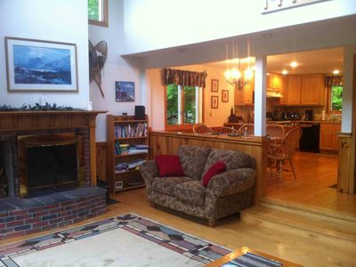 Living room with 40' flat screen TV and fireplace, fully-stocked kitchen