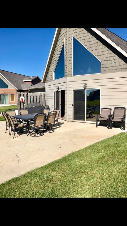 Over Sized Back Patio With Lots Of Patio Furniture For Guests To Relax On