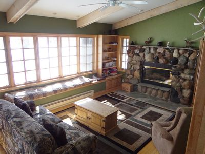 Warm and cozy family room with stone firepl,sofa w/bed, movies, books and games