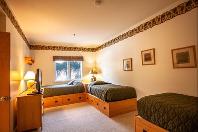Three twin beds in one of the guest bedrooms