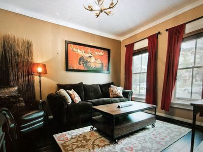 living room with gas stove heater, sofa with pull-out bed, flat screen TV