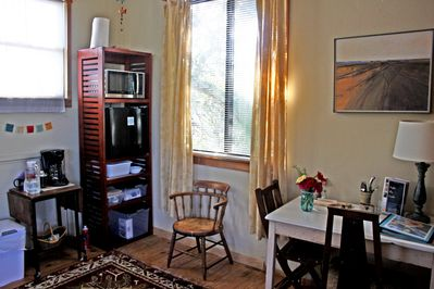 Mini refrigerator, microwave, coffee maker, and dining table.