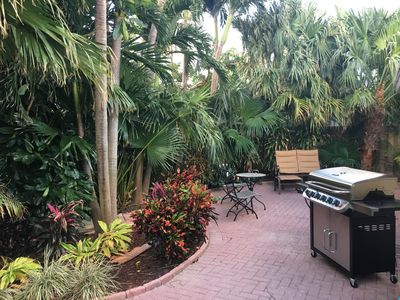 Grill Out in this Beautiful Backyard Adorned By Palm Trees and Tropical Plants
