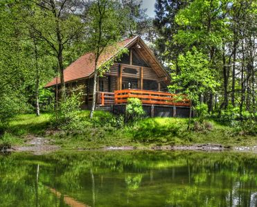 Photo for Romantic log cabin on a small idyllic forest lake