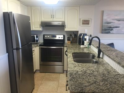 Full kitchen with stainless steel appliances and granite countertops.