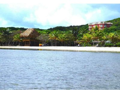View of condo building, beach & palapa from water