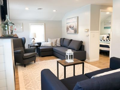 Spacious living room with plenty of seating, a flat screen TV and fireplace.