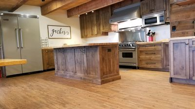 High end cabinets paired with Viking range, oven and hood, and microwave. Miele dishwasher and Wolf ice machine. Refrigerated drawer and freezer drawer located to the left of the gas range. Butcher block countertops.