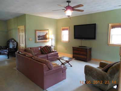 Large living area with large screen TV.  Ceiling fans through out the cabin.