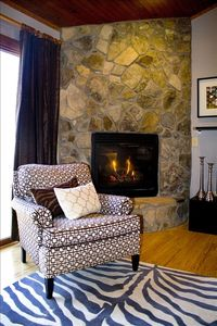 Relaxing by the stone fireplace. Beautifully decorated and modern furniture.