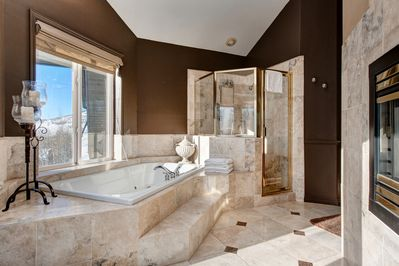 Master Bath - The wraparound gas fireplace leads into the en-suite bath, with a soaking tub and walk-in shower