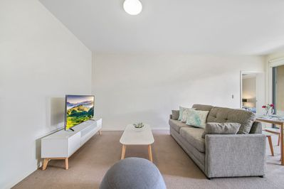 A living area with a 2-seater sofa and a flat screen TV.