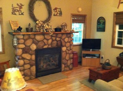 Living room with stone gas fireplace and flat screen TV