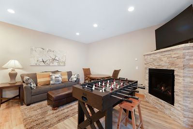 """Game Room  - The downstairs game room offers a foosball table, 55"""" TV, and gas fireplace."""