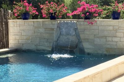 THE POOL - A RAISED EDGE POOL ALLOWS EVERYONE TO HAVE A SEAT EATING, DRINKING AND RELAXING POOLSIDE. NOTHING BEATS THE FLOWERS THAT BLOOM POOLSIDE.
