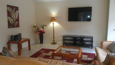 Spacious Living room with a 52 inch flat screen TV , DVD and stereo system