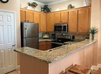 Fully equipped kitchen with dining bar & separate storage pantry closet.