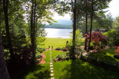 View from lake house deck looking toward lake and owner' dock in summer.