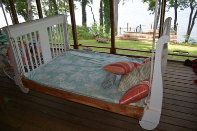 Queen-size hanging bed on spacious  porch is wonderful for napping and reading.