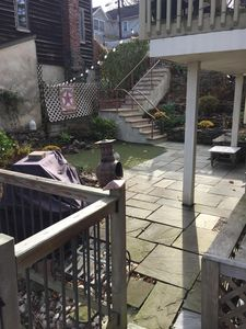 Private courtyard leading to large deck overlooking bridge and stream