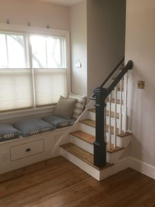 New entryway and re-oriented  interior staircase with window seat.