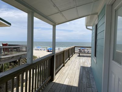 Entry to cottage with view of ocean, deck and picnic table.