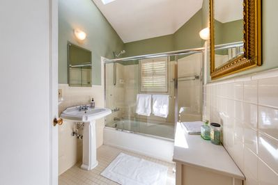 Charming bath with skylight, pedestal sink, and shower/tub combo