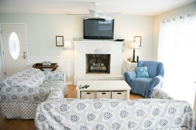 comfy couch and rocking chair with large flat screen and fireplace