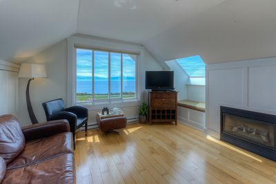 Living room with TV, gas fireplace and unobstructed panoramic ocean views
