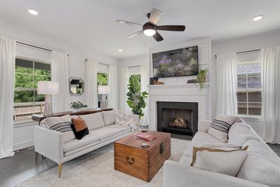 With modern white sofas, lush curtains, a multitude of windows, a fireplace, and