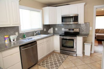Kitchen with electric stove/oven, microwave, dishwasher, and other appliances