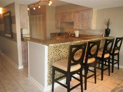 Fully Stocked Kitchen with granite countertops and breakfast bar with glass tile