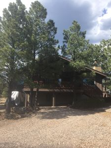 Rustic Cabin with modern amenities, large front deck surrounded by pine trees.