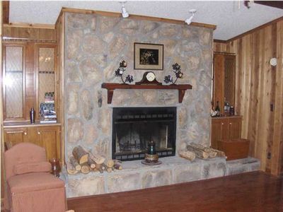 Stone fireplace flanked by gun cabinets