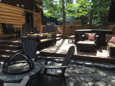 outdoor patio with fire pit dining table couches and hot tub