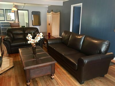 Fully furnished living room with leather couches & wood floors