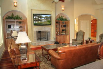 Large family room with lrg flatscreen, wood burning fireplace, stereo, pool view