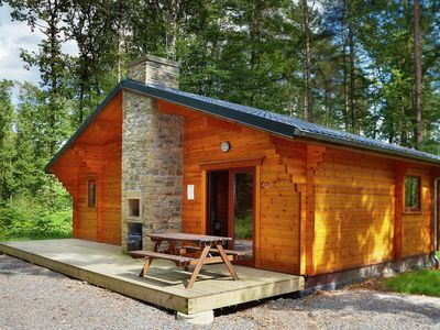 Photo for Detached wooden chalet with an open fireplace and a bathtub in a wooded park