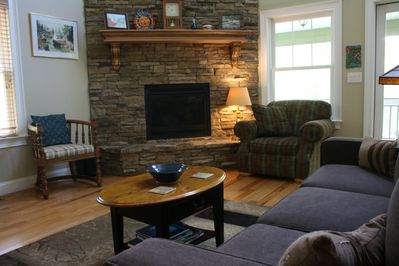 The spacious living room with a gas stack-stone fireplace.