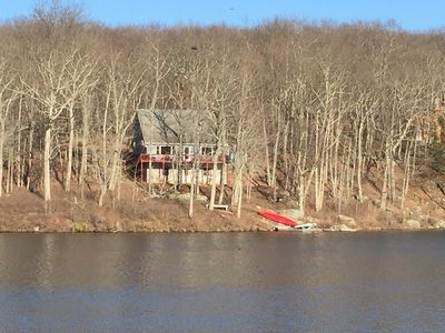 Lovely view of this lakefront home nestled in the woods on a cold winter day.