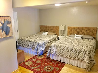 Downstairs bedroom with two queen beds, TV, and private full bath.