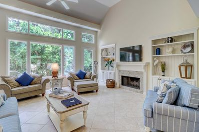 Large family room with new furnishings (including queen sleep sofa), wall-mounted flat panel TV, fireplace that is decorative only, large windows for lots of natural light, and vaulted ceilings