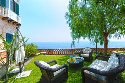 Private garden  with sea view and furnished with sofa and umbrella
