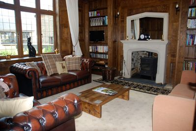 Wood panelled drawing room with gothic stone fireplace and wood burning stove