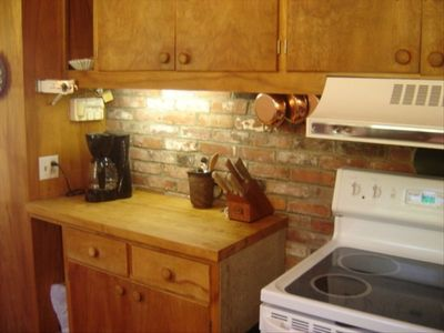 Part of main kitchen area, classic maple wood cabinets and butcher block counter