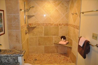 Walk in shower with tumbled travertine walls and luxury rainfall showerhead.