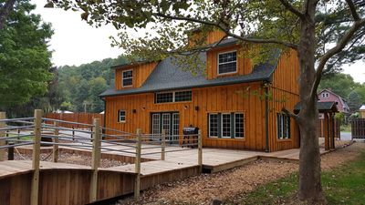 Front of Eagle Creek Lodge with a huge deck and bridge to fire pit.