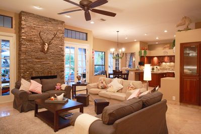 Living Room and Kitchen - Open floor plan makes for fantastic entertaining with family and friends -- all with large windows and doors out to the patio, pool and spa!