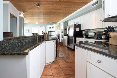 Custom kitchen with granite countertops, fully stocked, plenty of storage.