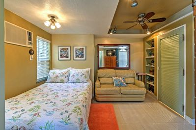 Comfortable full-sized bed and a leather loveseat underneath a gorgeous Mirror
